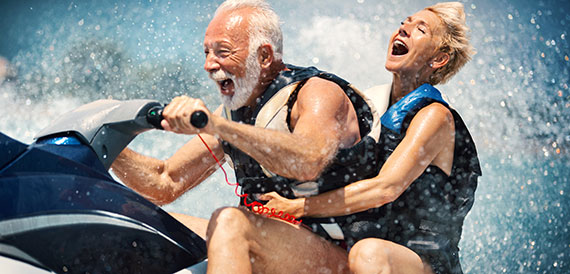 Elderly couple having a blast riding a jet ski.